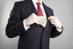 Corruption. Man putting money in suit jacket pocket. Corruption in business. Man putting american dollars in suit jacket pocket. Clipping path included Stock Photo