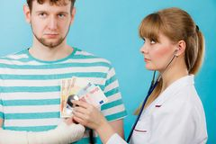 Female doctor checking heart beating. Corruption in medicine. Female doctor with stethoscope checking heart beating. Male bandaged hand with banknotes euro royalty free stock photo