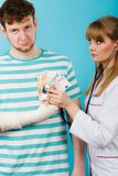 Female doctor checking heart beating. Corruption in medicine. Female doctor with stethoscope checking heart beating. Male bandaged hand with banknotes euro stock photo