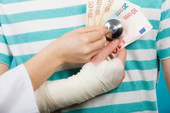Female doctor checking heart beating. Corruption in medicine. Female doctor with stethoscope checking heart beating. Male bandaged hand with banknotes euro royalty free stock images