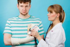 Female doctor checking heart beating. Corruption in medicine. Female doctor with stethoscope checking heart beating. Male bandaged hand with banknotes euro money royalty free stock images