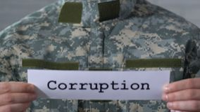 Corruption written on paper in soldier hands, justice in military institution. Stock footage stock video