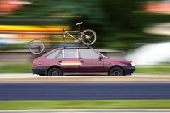 Corsa in automobile e bici Fotografie Stock
