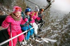 Corsa con gli sci, ascensore di sci, stazione sciistica - sciatori felici della famiglia sull'ascensore di sci Immagini Stock