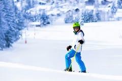 Corsa con gli sci del bambino in montagne Immagini Stock