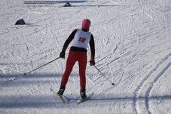 Corsa con gli sci del bambino in montagne Bambino attivo del bambino con il casco, gli occhiali di protezione ed i pali di sicure fotografia stock libera da diritti