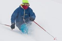 Corsa con gli sci del giovane nella bufera di neve Immagine Stock
