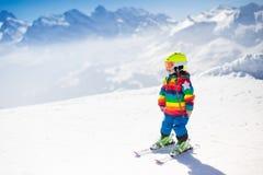 Corsa con gli sci del piccolo bambino nelle montagne Immagini Stock