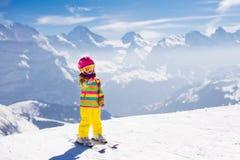 Corsa con gli sci del piccolo bambino nelle montagne Fotografia Stock