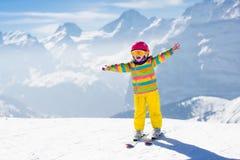 Corsa con gli sci del piccolo bambino nelle montagne Immagine Stock