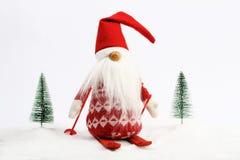 Corsa con gli sci dell'assistente di Natale (elfo) sulla neve dopo due alberi nevosi rossi e colori bianchi Immagini Stock Libere da Diritti