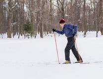 Corsa con gli sci dell'uomo anziano nella neve di inverno del paese trasversale Fotografia Stock