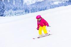 Corsa con gli sci della bambina nelle montagne Fotografia Stock