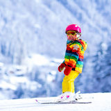 Corsa con gli sci della bambina nelle montagne Immagine Stock