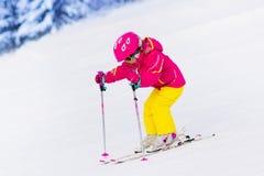Corsa con gli sci della bambina nelle montagne Immagini Stock Libere da Diritti
