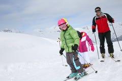 Corsa con gli sci della famiglia sui pendii Fotografia Stock Libera da Diritti