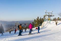 Corsa con gli sci della famiglia sulla pista Fotografie Stock Libere da Diritti