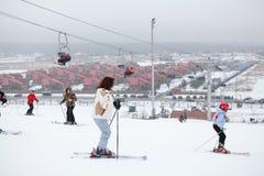 Corsa con gli sci della gente sui pendii Immagini Stock