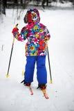 Corsa con gli sci della ragazza del bambino un giorno di inverno luminoso Immagini Stock
