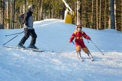 Corsa con gli sci di addestramento della ragazza con suo padre Immagini Stock Libere da Diritti