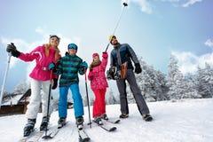 Corsa con gli sci di sport della famiglia e tempo di snowboard il giorno soleggiato Fotografie Stock