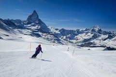 Corsa con gli sci femminile dello sciatore sui pendii della montagna del Cervino Fotografia Stock