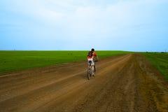 Corsa della bici di montagna sulla strada a terra Fotografie Stock Libere da Diritti