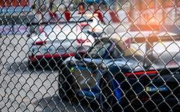 Corsa di automobile del Motorsport sulla strada asfaltata Vista dal reticolato della maglia del recinto sull'automobile vaga sul  fotografie stock