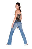 Corset and Blue Jeans. Adult woman in a black and gold corset and tight fitting blue jeans with her back to the camera looking over her shoulder Stock Photography