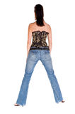 Corset and Blue Jeans. Adult woman in a black and gold corset and tight fitting blue jeans with her back to the camera Royalty Free Stock Image