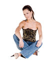 Corset and Blue Jeans. Mid adult woman in a black and gold corset and blue jeans sitting with her legs crossed Stock Photography