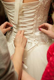 Corset rope tying on a wedding dress. Tying corset on white wedding dress with female hands Royalty Free Stock Photography