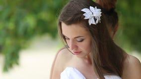 corsetto dai capelli del legame della sposa del fiore di aiuto di aiuti del vestito sulla spiaggia stock footage