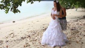 corsetto di aiuto del legame della sposa di aiuti del vestito da sposa sulla spiaggia archivi video