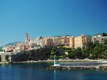 Corsica Bastia port view from sea on harbour with green lighthous church and old town blue sky. Background Royalty Free Stock Photo