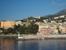 Corsica Bastia port view from sea on harbour with  green and old. Town houses yeachts and blue sky background Stock Photos
