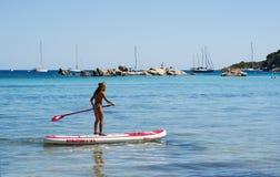 Corsica, Santa Giulia beach, sea, south, coastline, France, Europe, island, summer,. Corsica, 04/09/2017: a little girl on a paddle in the Mediterranean Sea at Stock Image