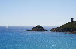 Corsica, beach, Genoese Tower, sea, south, coastline, France, Europe, island, summer,. Corsica, 04/09/2017: the Mediterranean Sea and the Genoese Tower on the Stock Photos