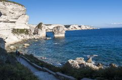 Corsica, Bonifacio, Strait of Bonifacio, beach, Mediterranean Sea, limestone, cliff, rocks, Bouches de Bonifacio. Corsica, 05/09/2017: people walking on the Royalty Free Stock Images