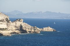 Corsica, Bonifacio, Strait of Bonifacio, Mediterranean sea, sailboat, cliff, rocks, Bouches de Bonifacio. Corsica, 05/09/2017: sailboats sailing in the Strait of Stock Images