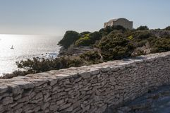 Corsica, Bonifacio, Strait of Bonifacio, beach, Mediterranean Sea, limestone, cliff, rocks, Bouches de Bonifacio, maquis. Corsica, 05/09/2017: stone building at Stock Photography