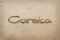 Corsica - written in sand on beach texture Royalty Free Stock Photos
