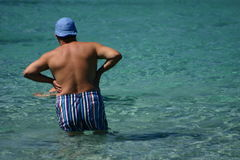 Corsican beach. Corsica   Bay of Calvi, blue hat  man  on the beach entering into the water Stock Images