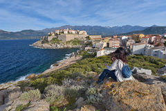 Corsican town Calvi. Calvi is a town in the north-west Corsica well known for the historical citadel. In the foreground a woman is sitting on the rock and Stock Photography