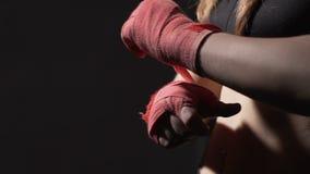 Corso dell'autodifesa, pugile tailandese di Muay della forte donna che avvolge fasciatura sulla sua mano stock footage