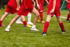 Corso di formazione di calcio per i bambini Giovani giocatori di football americano che allungano prima della partita Immagine Stock