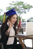Corso di formazione online - chiacchierata e sorriso felici della donna di affari con il grado di graduazione fotografie stock libere da diritti