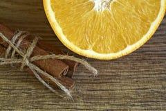 Cortó la naranja y los palillos de canela frescos foto de archivo libre de regalías