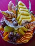 Cortó maravillosamente diversas frutas asperjadas con el azúcar en polvo fotografía de archivo libre de regalías