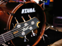Cort Bass Guitar. Headstock of five string Cort Bass with Tama bass drum Royalty Free Stock Photos